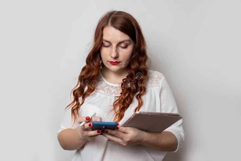 Una joven empresaria con un hermoso peinado rizado está usando un smartphone y sosteniendo una tableta Proyectos y concepto de tr fotos de archivo
