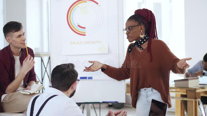 Una joven profesional y feliz mujer de negocios de África dando una charla, explicando un diagrama de finanzas a sus colegas de l foto de archivo