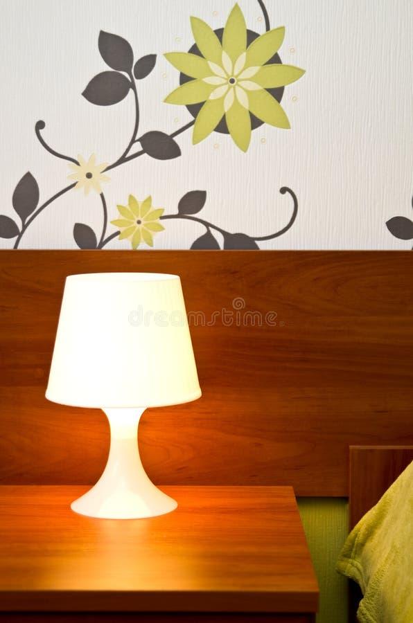 Una lámpara de cabecera encendida imágenes de archivo libres de regalías