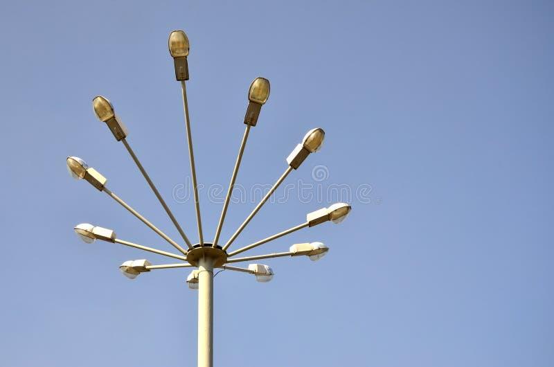 Una lámpara de calle que consiste en un alto pilar y varios plafonds para las fuentes de luz Vista inusual del alumbrado público  foto de archivo libre de regalías