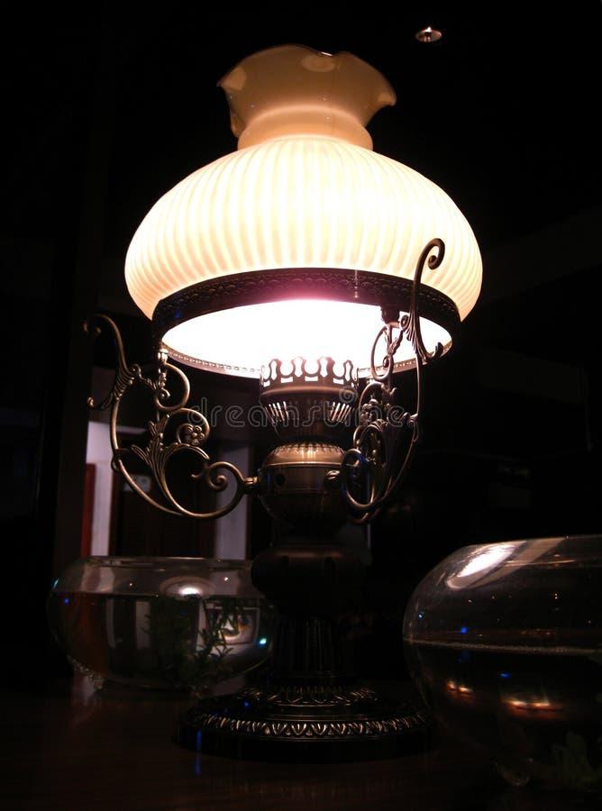Una lámpara de cobre amarillo pasada de moda elegante que brilla suavemente de la esquina oscura cerca de mi tabla en el restaura imagenes de archivo