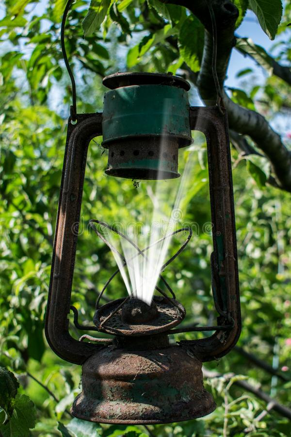 Una lámpara de gas vieja de la cual viene una luz blanca, como un alcohol fotografía de archivo