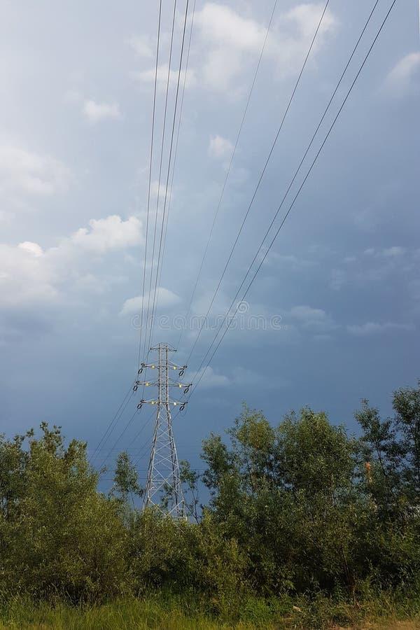 Una línea eléctrica de alto voltaje iluminada por la luz del sol contra un fondo de nubes de un cielo tempestuoso Transporte de l imagenes de archivo