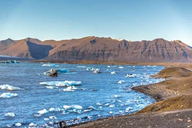 Una laguna ha riempito di iceberg di galleggiamento, montagne nei precedenti, il giorno del cielo blu fotografie stock libere da diritti
