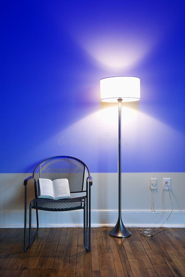 Una lampada e una presidenza con un libro. immagine stock