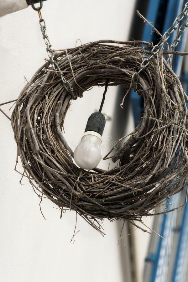 Una lampadina che pesa in una corona riccia di legno immagini stock libere da diritti