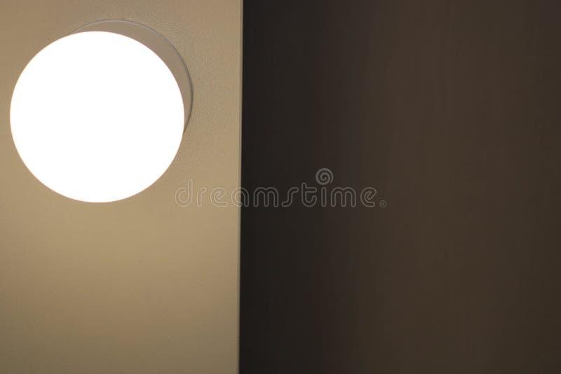 Una lampadina rotonda bruciante bianca opaca d'ardore luminosa su uno spazio sinistro e scuro sulla giusta vista vicina immagini stock libere da diritti