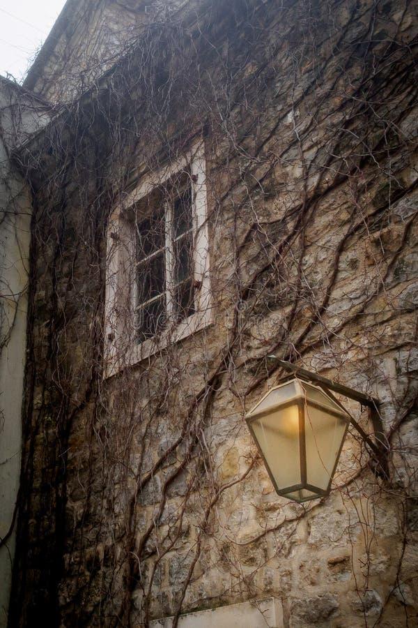 Una lanterna illumina una parete di pietra con una piccola finestra bianca nella vecchia città fotografia stock libera da diritti