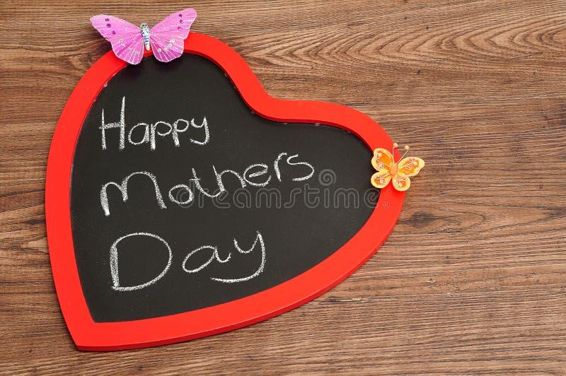 Una lavagna di forma del cuore con un messaggio felice di giorno di madri immagini stock libere da diritti