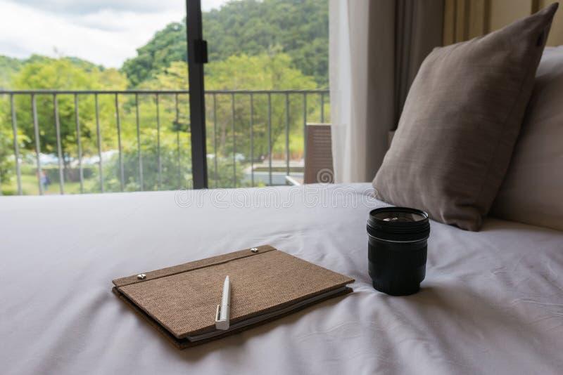 Una lente de cámara, una pluma y un cuaderno en la cama foto de archivo