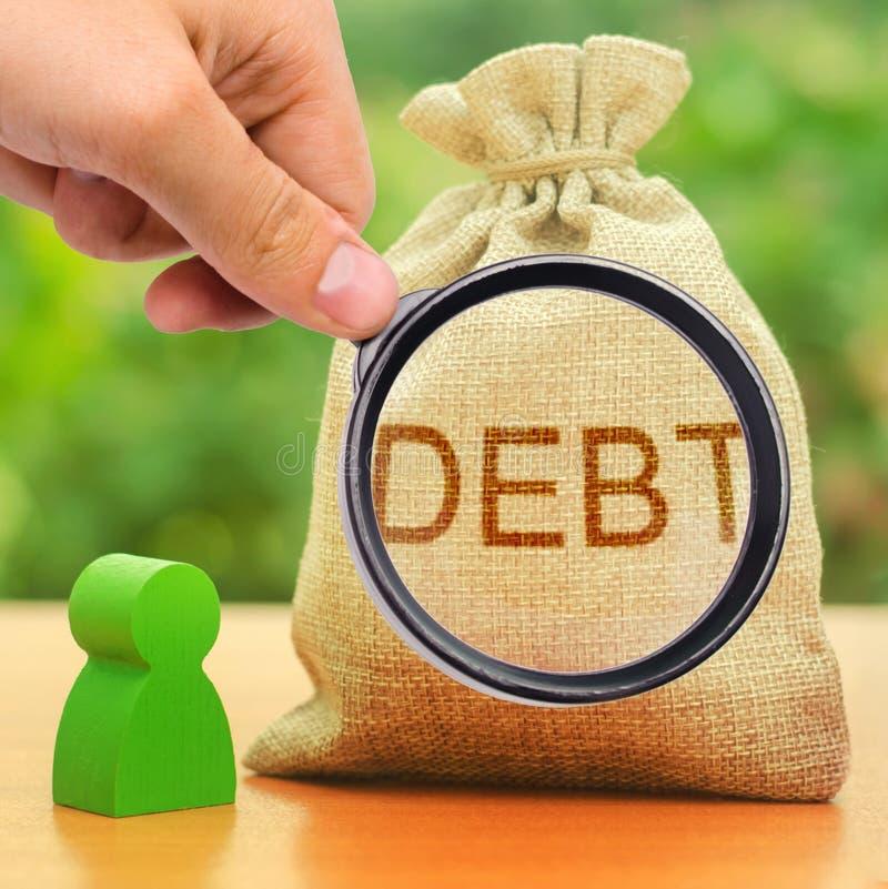 Una lente di ingrandimento guarda un sacchetto con DEBITO di iscrizione Obbligazioni non chiuse tra due persone, debiti finanziar immagini stock