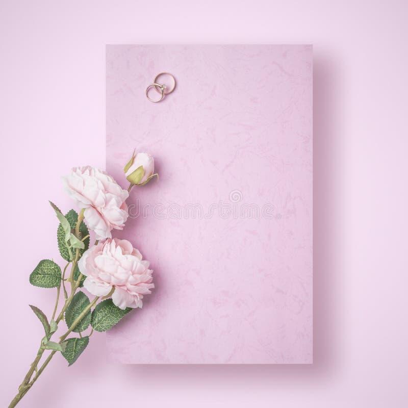 Una letra de amor romántica que debe todavía ser escrita con los anillos de bodas y subió en fondo rosado fotos de archivo