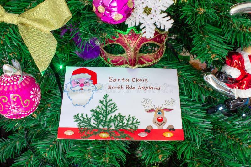 Una letra a Santa Claus en el Polo Norte en Laponia miente con los juguetes y los ornamentos y en el árbol de navidad imagen de archivo