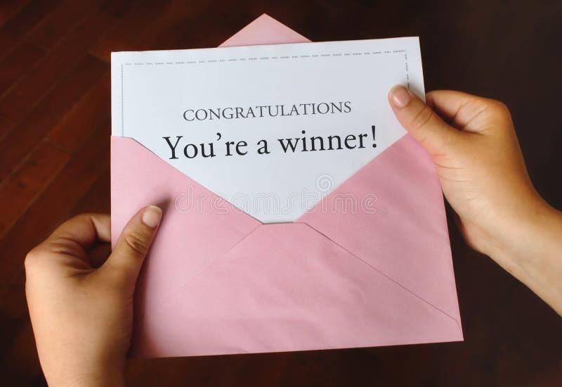 Una lettera che dice le congratulazioni siete un vincitore! con le mani che tengono una busta rosa fotografia stock