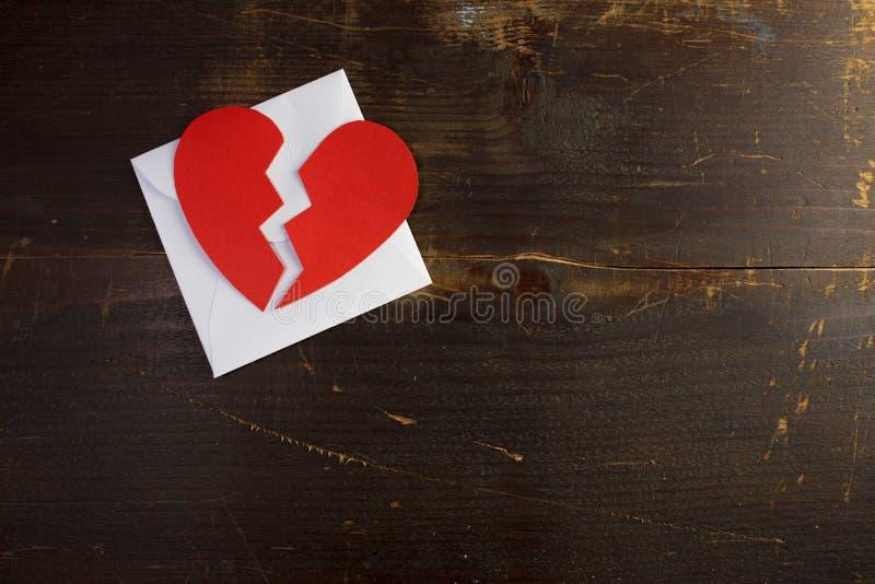 Una lettera della busta del biglietto di S. Valentino dello smembramento con un cuore rosso rotto immagini stock libere da diritti