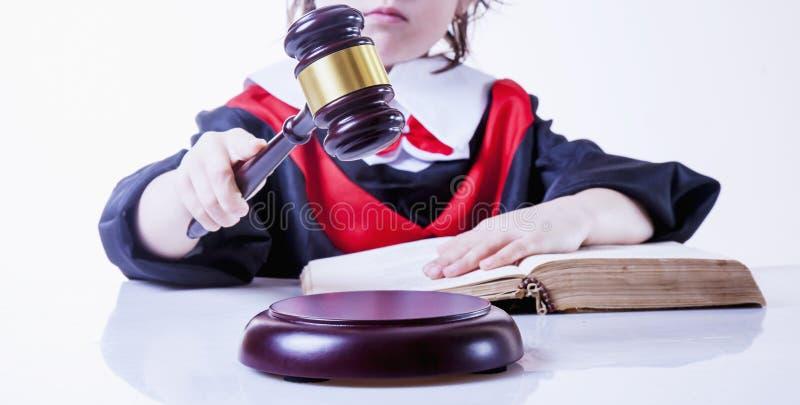 Una ley para todo el concepto Abogado serio del juez de la muchacha del pequeño niño que toma la decisión Foto chistosa fotos de archivo