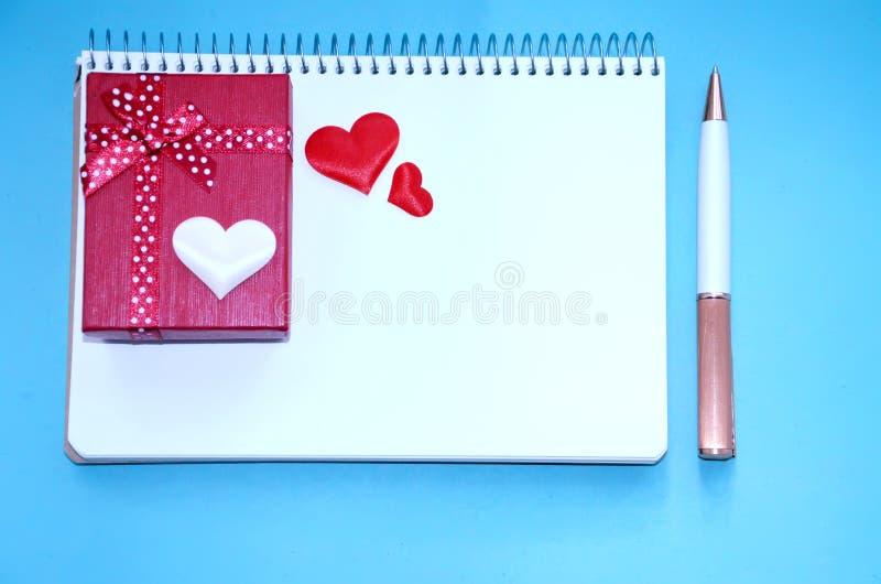 Una libreta, una caja de regalo, corazones y una pluma en el fondo azul imagenes de archivo