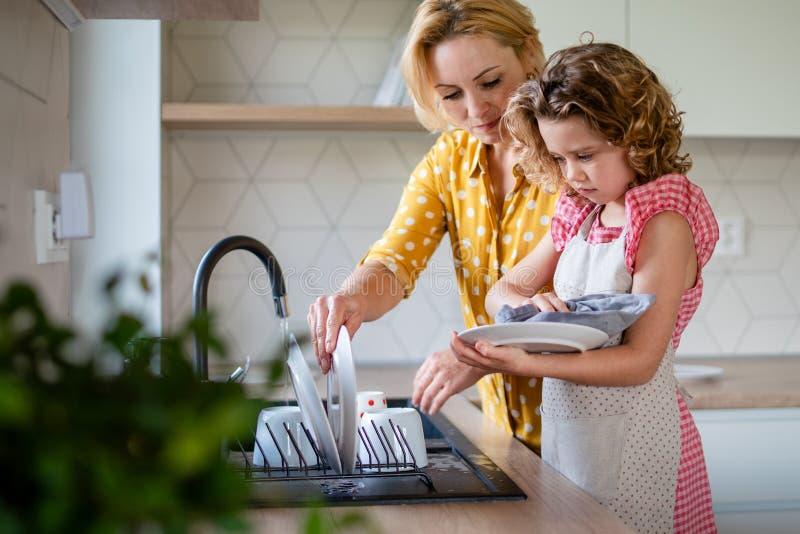 Una linda niña pequeña con madre dentro de la cocina en casa, lavando platos fotografía de archivo