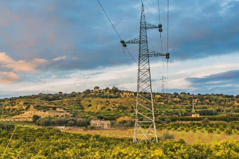 Una linea elettrica nella bella valle verde sui precedenti del cielo blu con le nuvole rosa al tramonto immagine stock