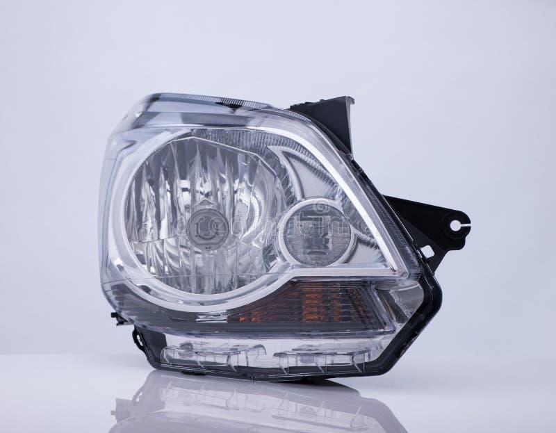 Una linterna del coche en el fondo blanco con la reflexión fotografía de archivo