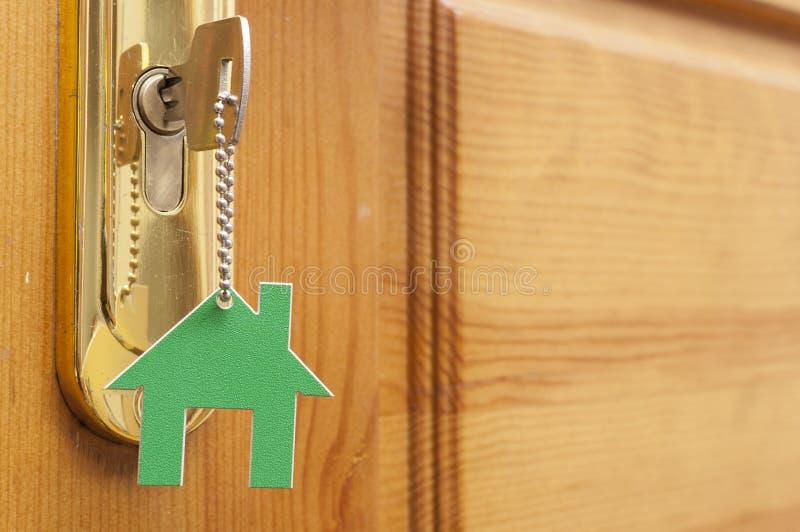 Una llave en una cerradura con el icono de la casa en ?l imágenes de archivo libres de regalías