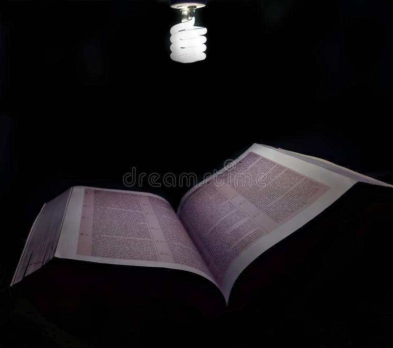 Una luce con il libro fotografie stock