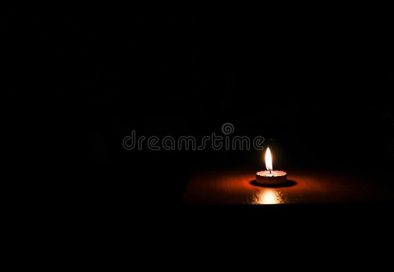 Una luce della candela su fondo nero fotografia stock