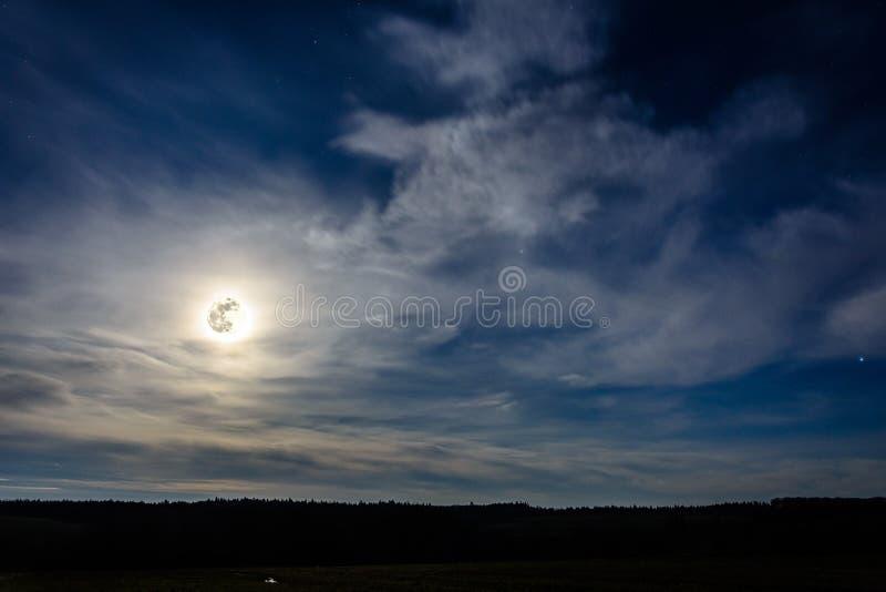 Una Luna Llena maravillosa ha descendido sobre el ucraniano Cárpatos en nubes borrosas foto de archivo
