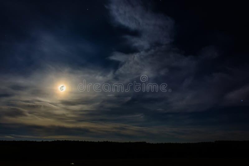 Una Luna Llena maravillosa ha descendido sobre el ucraniano Cárpatos en nubes borrosas fotografía de archivo