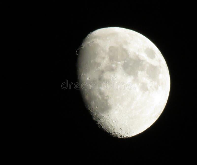 Una luna que brilla intensamente en un cielo nocturno negro al principio de la primavera imagen de archivo libre de regalías