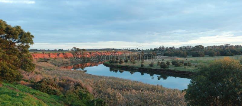 una lunga curva stirante in un fiume che passa attraverso rocce rosse e nell'oceano a Werribee sud durante l'ora d'oro, Victoria fotografie stock libere da diritti