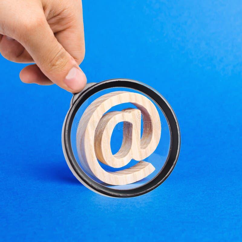 Una lupa mira un icono de correo electrónico sobre fondo azul correspondencia por Internet Contactos para el negocio Herramientas imagen de archivo