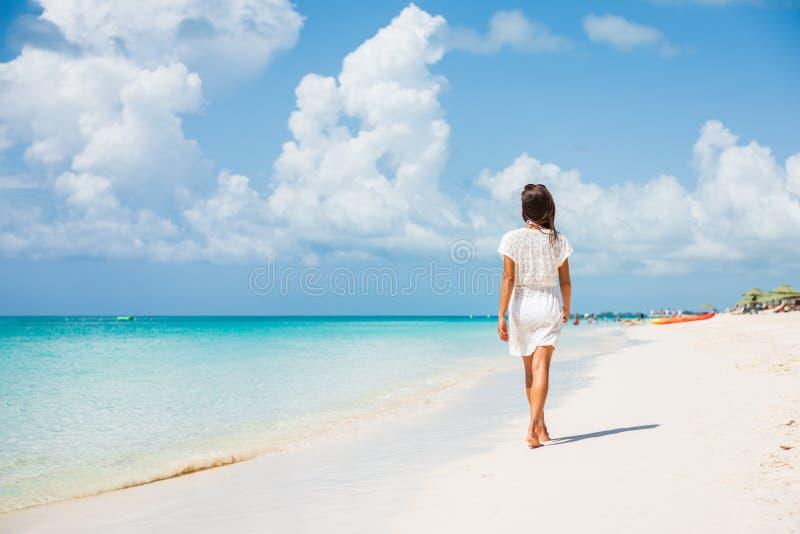 Una lussuosa vacanza estiva sulla spiaggia caraibica, donna che cammina verso una perfetta destinazione turistica fotografia stock libera da diritti