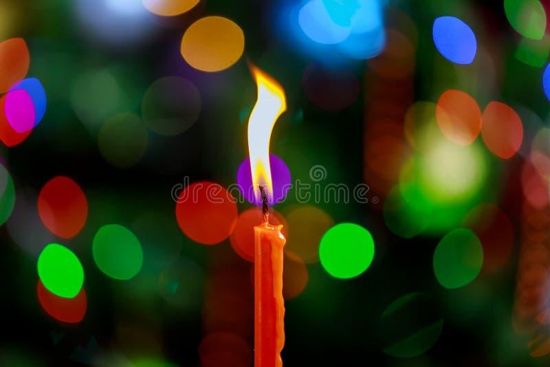 Una luz de la llama de vela en la noche con el bokeh en fondo oscuro foto de archivo