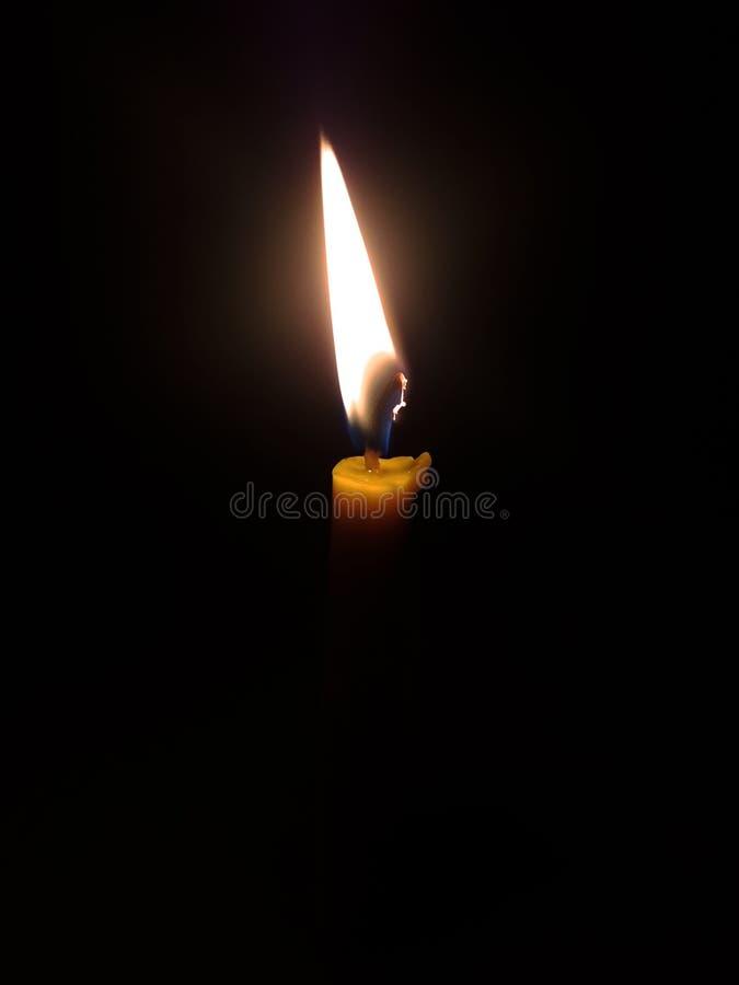 Una luz de la vela con el fondo negro imagenes de archivo