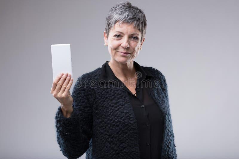 Una más vieja mujer atractiva que soporta un teléfono móvil fotos de archivo libres de regalías