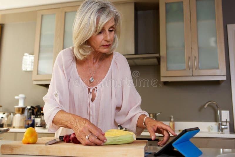Una más vieja mujer en la cocina que busca para la receta en la tableta digital fotos de archivo libres de regalías