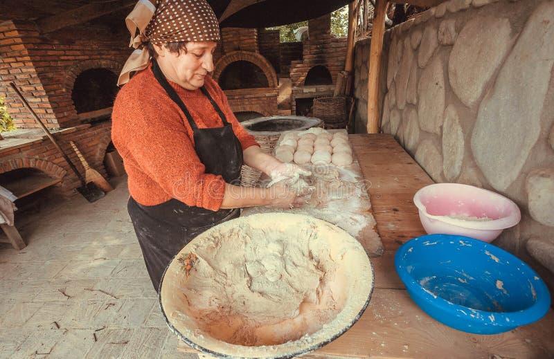 Una más vieja mujer que cuece el pan hecho en casa en su cocina de la casa en estilo del pueblo rural con el horno de piedra foto de archivo