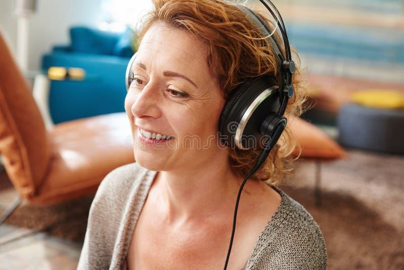 Una más vieja mujer que escucha la música con los auriculares en casa fotos de archivo libres de regalías