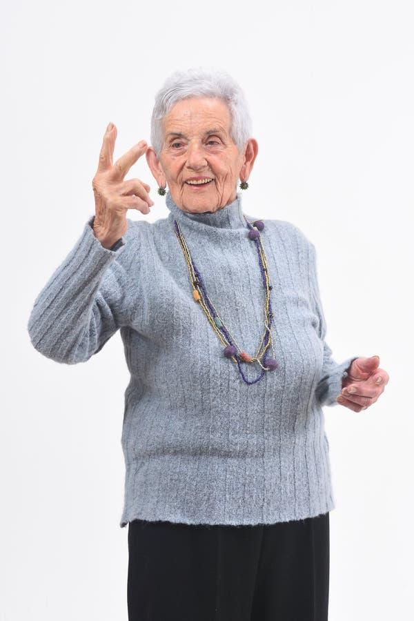 Una más vieja mujer que hace la muestra de la victoria en un fondo blanco fotografía de archivo libre de regalías