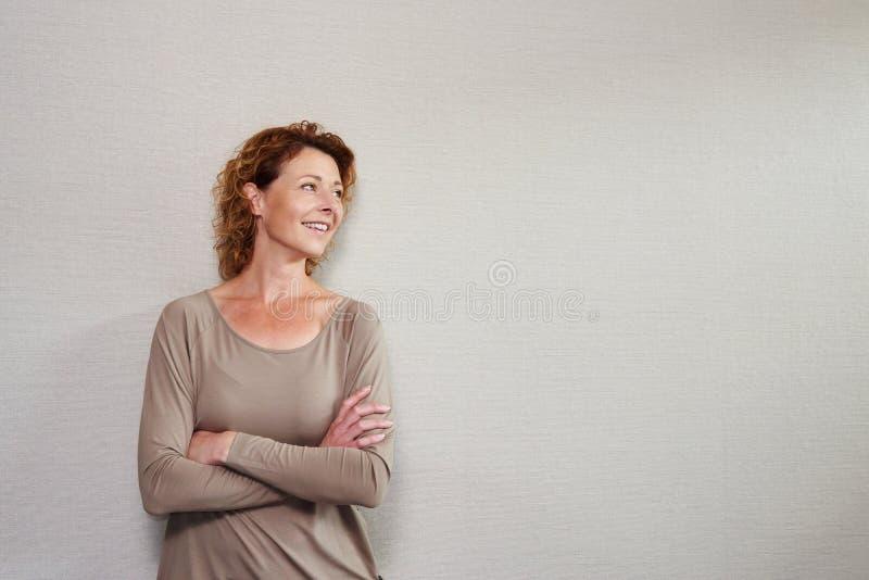 Una más vieja mujer que se colocaba con los brazos cruzó la mirada lejos sonriente fotografía de archivo libre de regalías