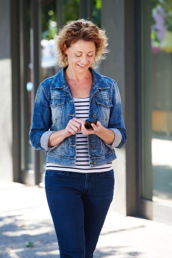 Una más vieja mujer que sonríe sosteniendo el teléfono elegante que camina en ciudad fotos de archivo libres de regalías