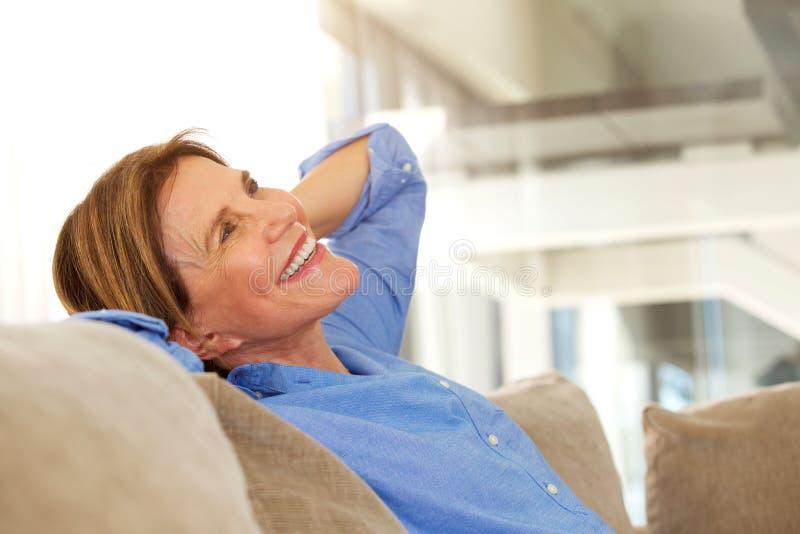 Una más vieja mujer que sonríe y que se relaja en casa imagen de archivo libre de regalías