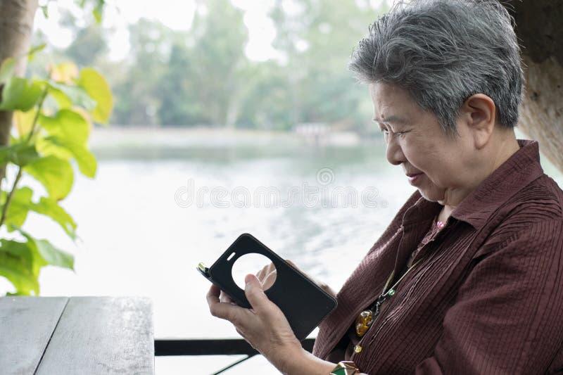 una más vieja mujer que sostiene el teléfono móvil en jardín texti femenino mayor fotografía de archivo