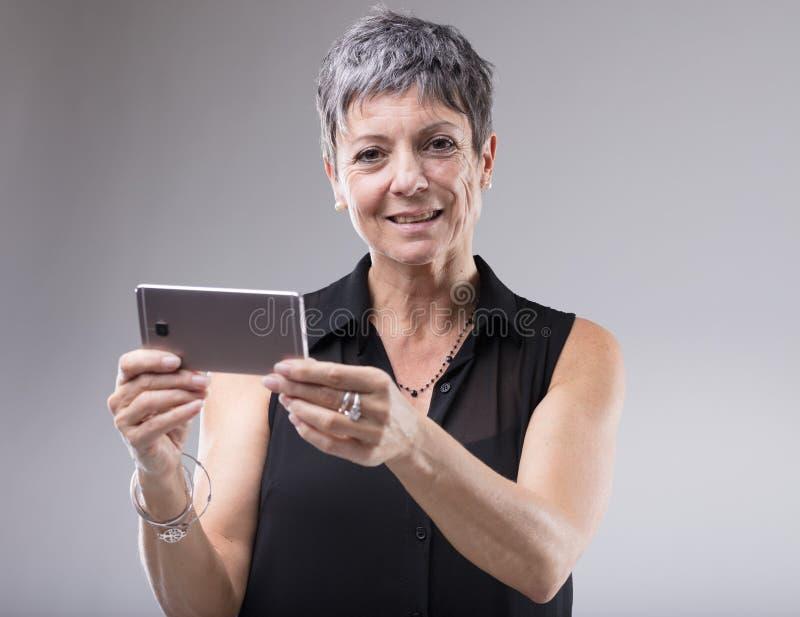 Una más vieja mujer que sostiene un teléfono móvil imagen de archivo libre de regalías