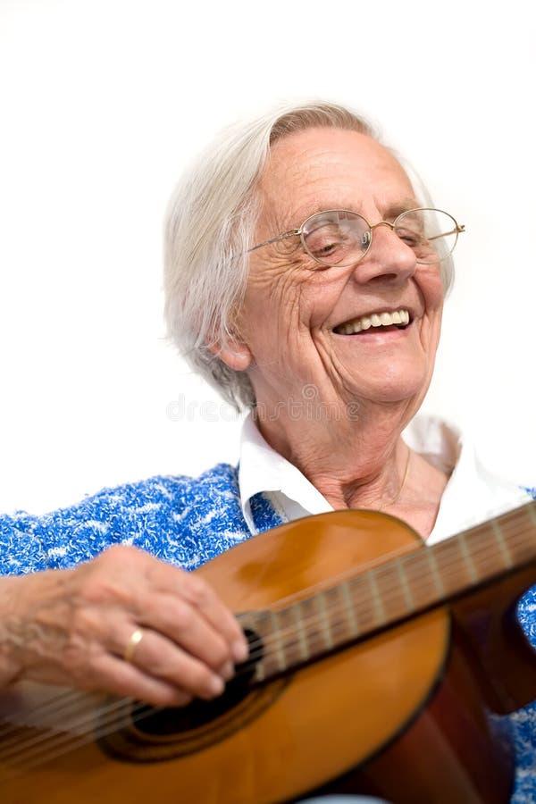 Una más vieja mujer que toca la guitarra. imagen de archivo
