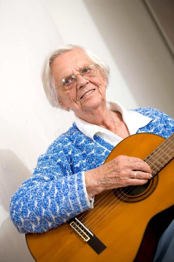 Una más vieja mujer que toca la guitarra. fotos de archivo