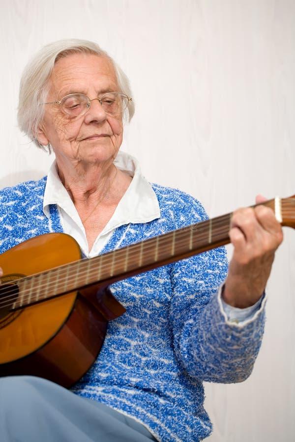 Una más vieja mujer que toca la guitarra. fotografía de archivo
