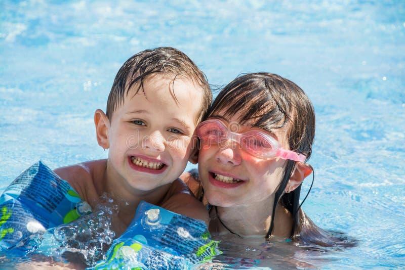 Una más vieja nadada de la hermana y del hermano menor en la piscina de los niños al aire libre imagenes de archivo
