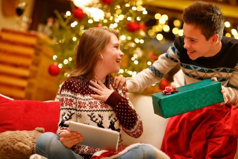Una más vieja sorpresa del hermano con el regalo de la Navidad su pequeña hermana fotos de archivo libres de regalías